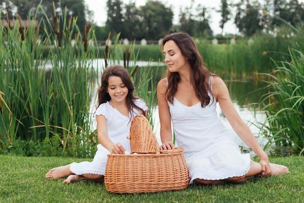 Madre e figlia con cestino da picnic in riva al lago