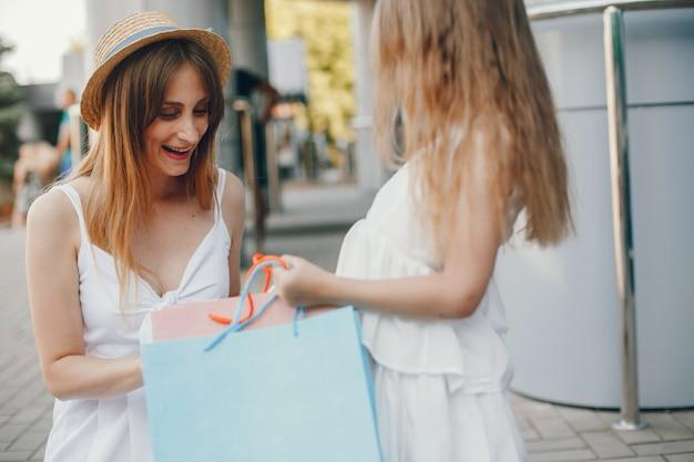 Madre e figlia con il sacchetto della spesa in una città