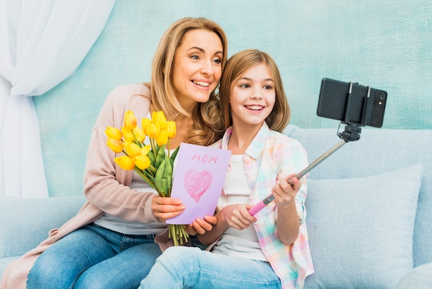 Madre e figlia con regali prendendo selfie