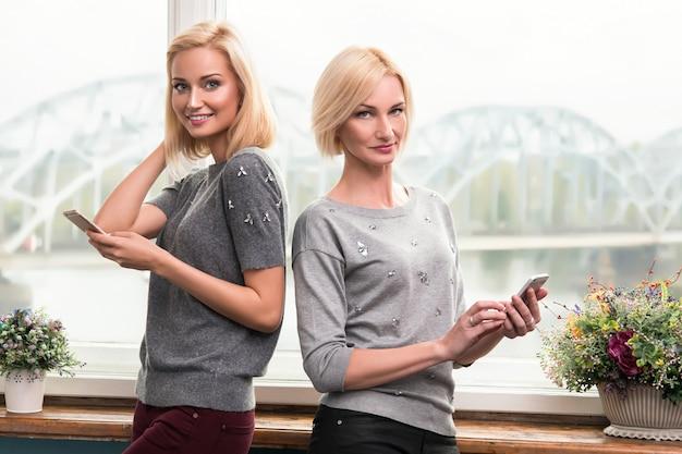 Madre e figlia con telefoni intelligenti