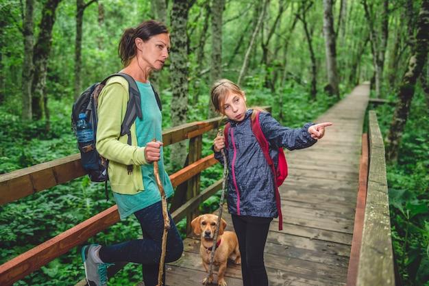 Madre e figlia con un cane che fa un'escursione nella foresta