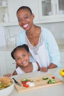 Madre e figlia del ritratto che producono insieme un'insalata