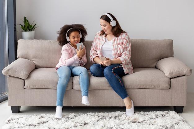 Madre e figlia di vista frontale che raffreddano a casa