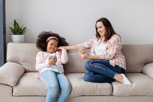 Madre e figlia di vista frontale che si rilassano a casa