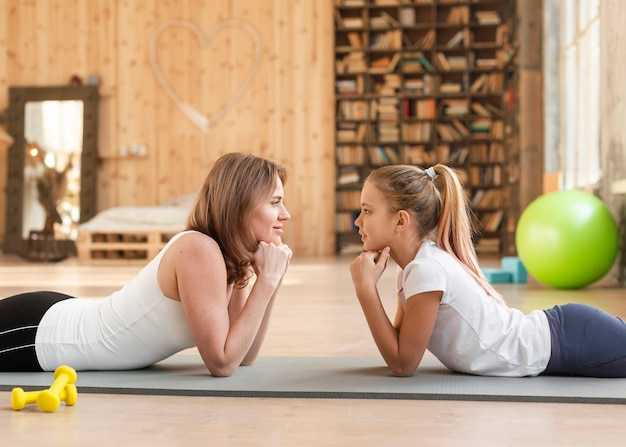 Madre e figlia di vista frontale che si siedono sulla stuoia che se lo esamina