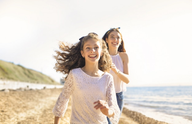 Madre e figlia divertirsi, in esecuzione in spiaggia
