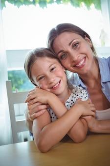 Madre e figlia felici che abbracciano a casa