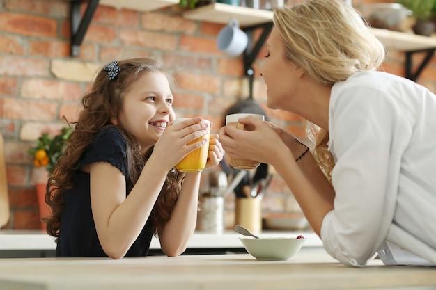 Madre e figlia felici che mangiano prima colazione nella cucina
