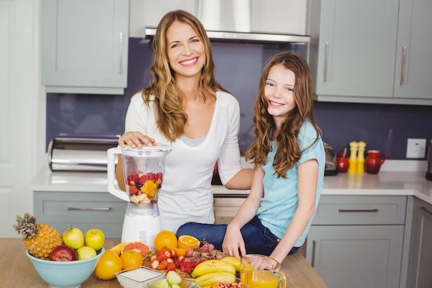 Madre e figlia felici che preparano un succo di frutta