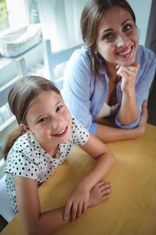 Madre e figlia felici che si appoggiano sul tavolo
