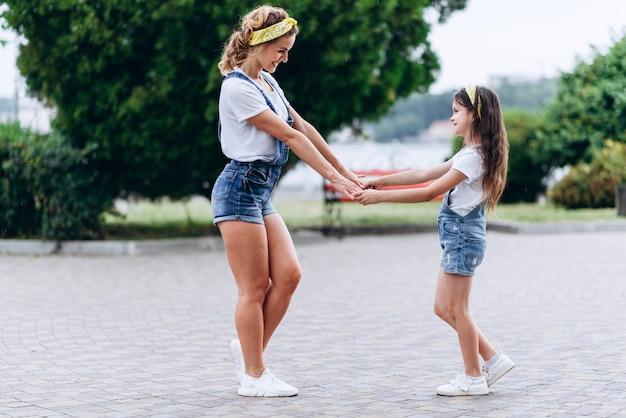 Madre e figlia felici che tengono a mano a mano e che si guardano all'aperto.