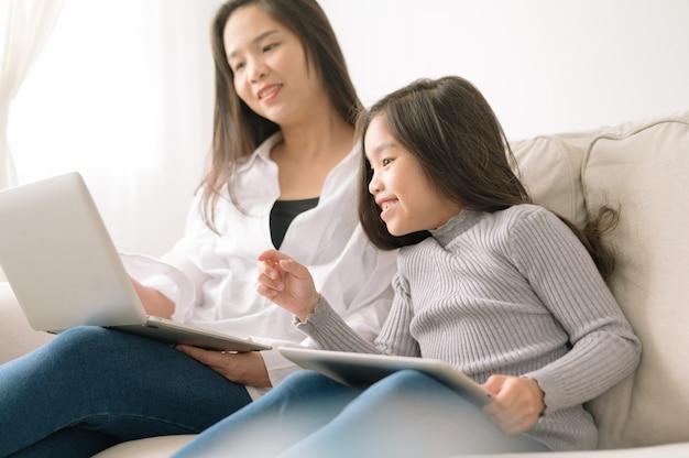 Madre e figlia felici con il pc della compressa e del computer portatile