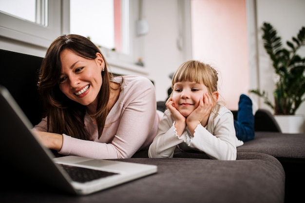 Madre e figlia godendo il tempo libero a casa. guardando i cartoni animati con la figlia.