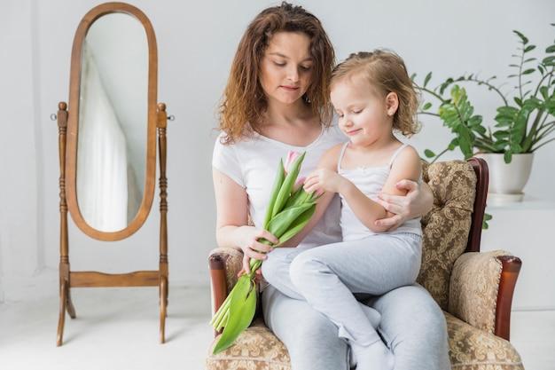 Madre e figlia graziose che si siedono insieme sulla sedia del bracciolo a casa