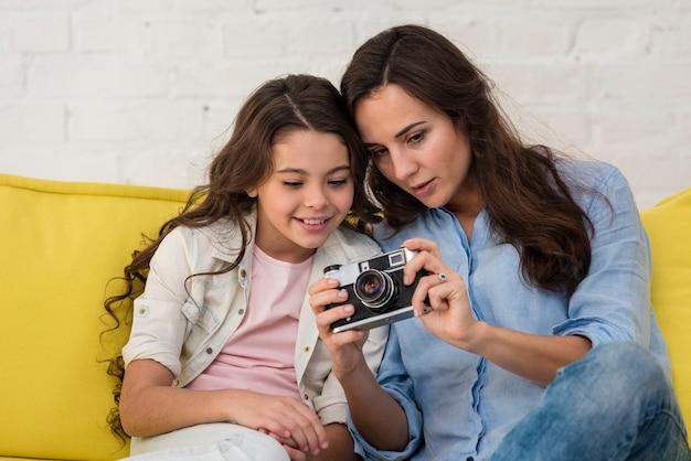 Madre e figlia guardando attraverso le foto