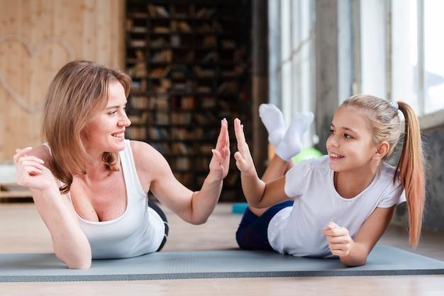 Madre e figlia high-fiving su stuoie di yoga