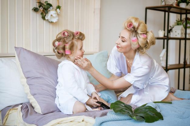 Madre e figlia in bigodini e una vestaglia sul letto