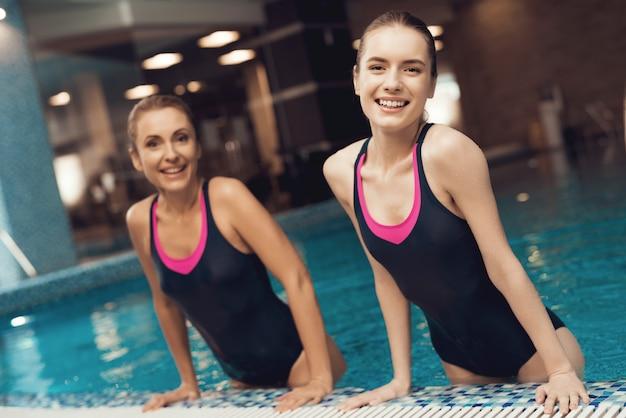 Madre e figlia in costumi da bagno al confine della piscina in palestra
