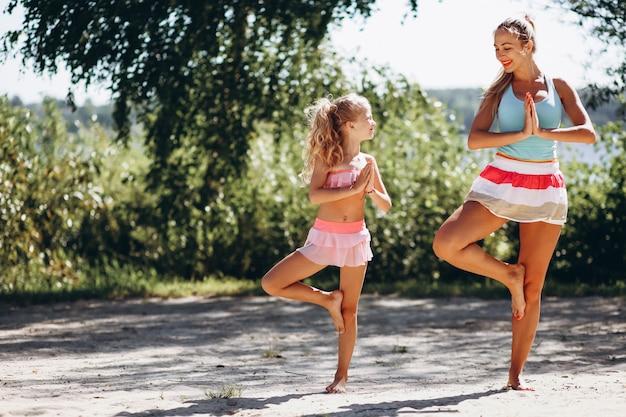 Madre e figlia in spiaggia praticando yoga