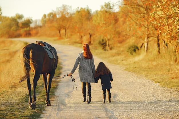Madre e figlia in un campo che gioca con un cavallo