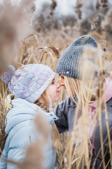 Madre e figlia in una passeggiata nella foresta, erba e neve, passeggiate invernali, foresta, campo, abiti invernali