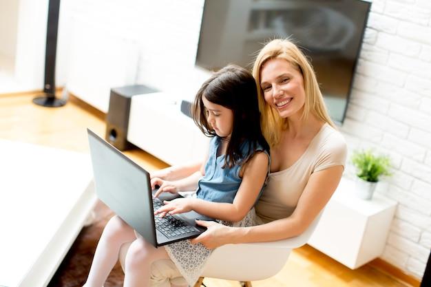 Madre e figlia insieme al computer portatile