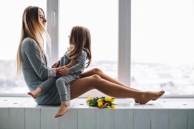 Madre e figlia insieme davanti alla finestra