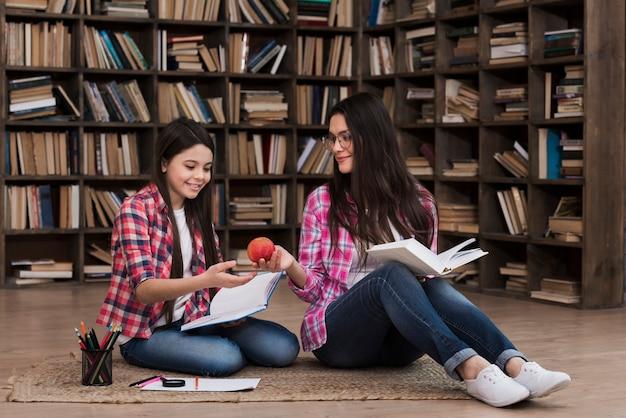 Madre e figlia insieme in biblioteca