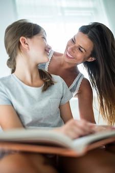 Madre e figlia interagente mentre libro di lettura sul letto