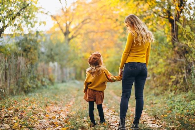 Madre e figlia nel parco pieno di foglie