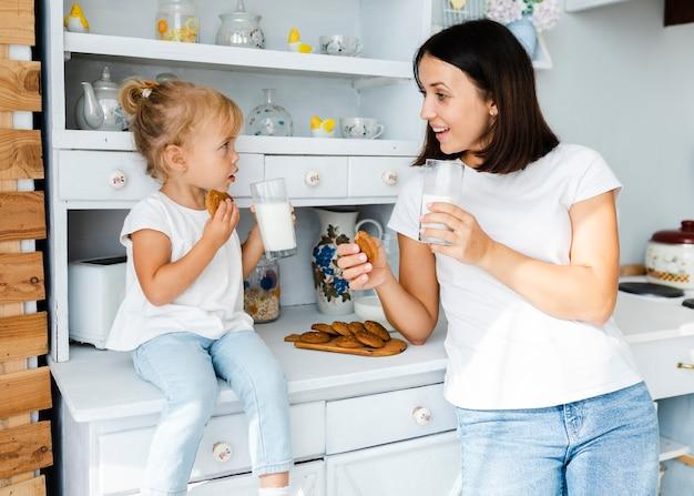 Madre e figlia piccola bere latte