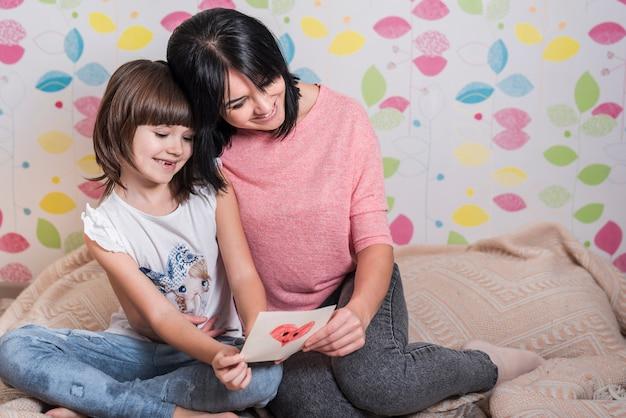 Madre e figlia piccola lettura di auguri