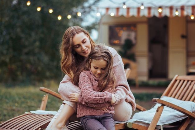 Madre e figlia piccola rilassarsi e divertirsi in campagna in vacanza camper