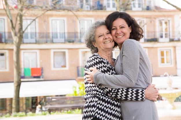 Madre e figlia positive felici che stanno per macchina fotografica