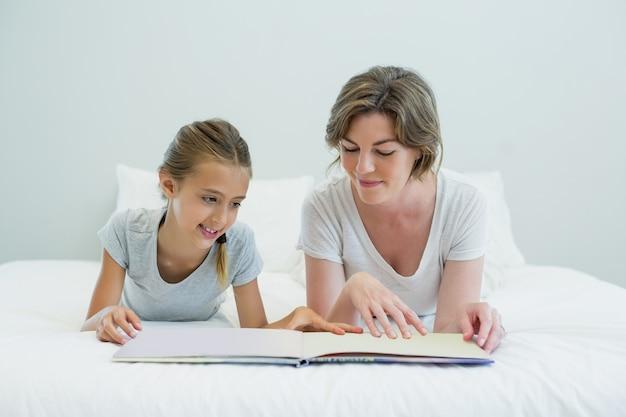Madre e figlia sdraiata sul letto e leggere il libro