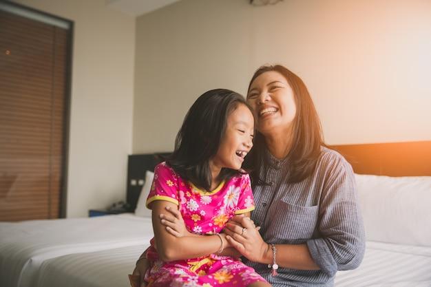 Madre e figlia si divertono a giocare sul letto