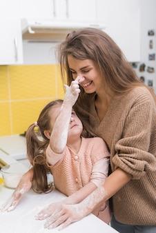 Madre e figlia si divertono con la farina