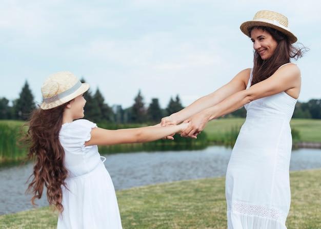 Madre e figlia si tengono per mano in riva al lago