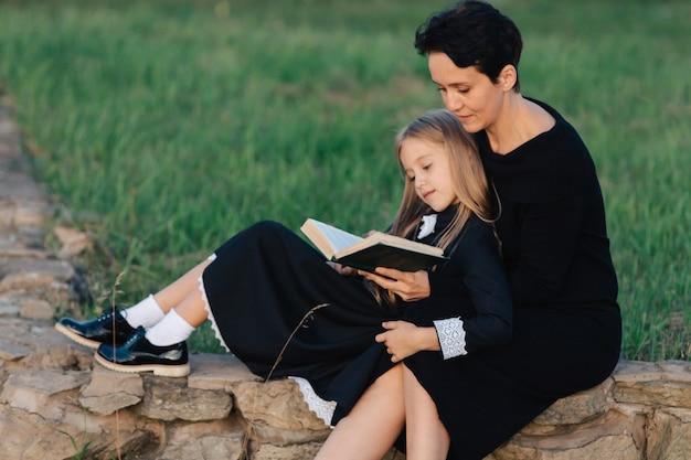 Madre e figlia sono seduti su una panchina di pietra e leggono un libro. donna con un bambino in abiti neri.