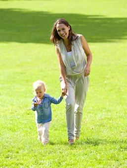 Madre e figlia sorridenti che camminano sull'erba