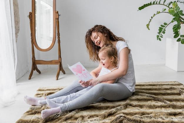 Madre e figlia sorridenti che si siedono sul tappeto lanuginoso che guarda cartolina d'auguri nella casa