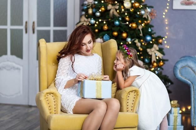Madre e figlia sorridenti con il contenitore di regalo
