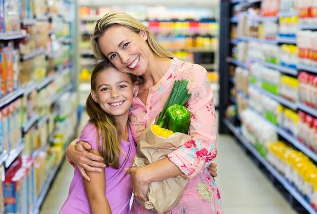 Madre e figlia sorridenti con il sacchetto di drogheria