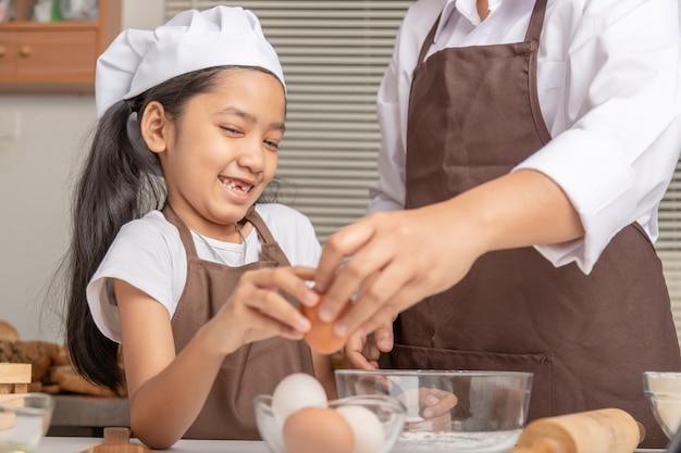 Madre e figlia stanno aiutando a raccogliere le uova per cucinare con felicità