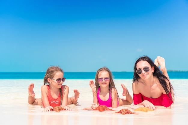 Madre e figlie che godono del tempo in spiaggia tropicale