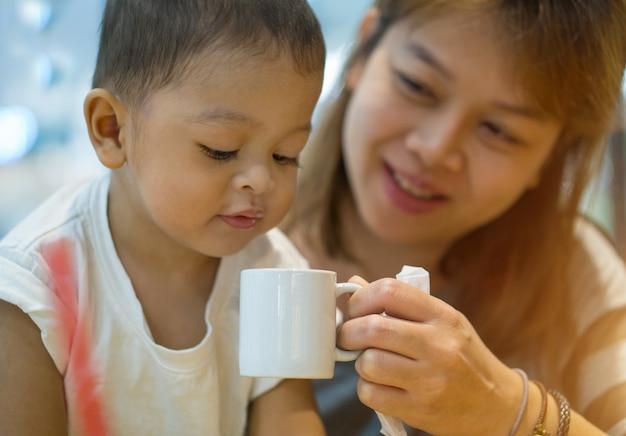 Madre e figlio asiatici. la madre è stata sollevata una tazza di acqua bianca.