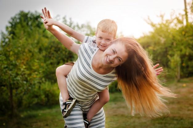 Madre e figlio caucasici felici all'aperto nel parco il giorno di molla soleggiato