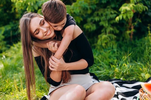 Madre e figlio che hanno un picnic nel parco e nell'abbracciare