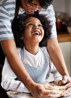 Madre e figlio che impastano la pasta in cucina