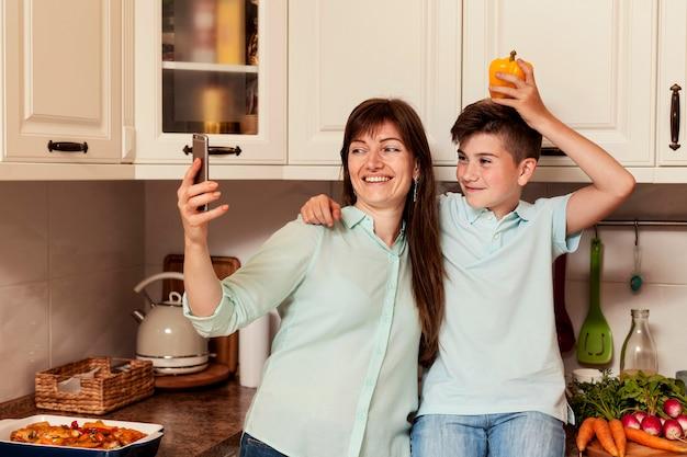 Madre e figlio che prendono selfie in cucina